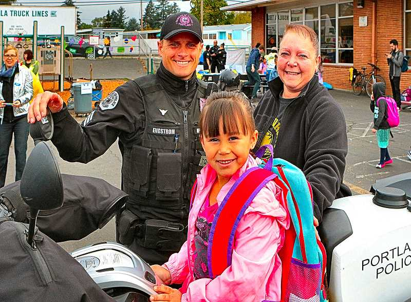 DAVID F. ASHTON - On a Portland Police Traffic Division motorcycle, Sergeant Ty Engstrom helped Aubreecy Dobson to sit in the saddle, while Grandma Wendy Marringer looked on.