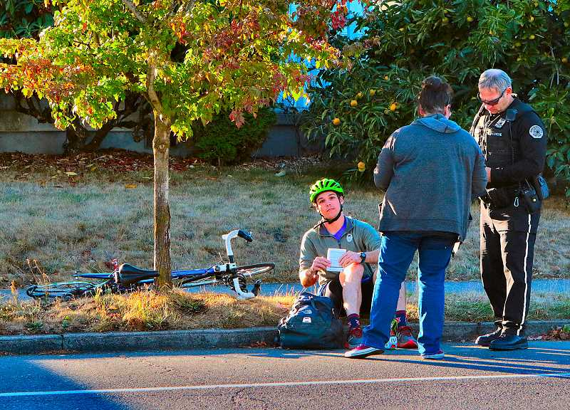 DAVID F. ASHTON - A police officer helps the vans driver and the bumped bike rider exchange information.