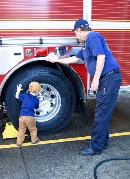 OUTLOOK PHOTO: MATT DEBOW  - Isaiah Warren, 2, washes a wheel well with the the help of Corbett Fire District Chief Dave Flood.