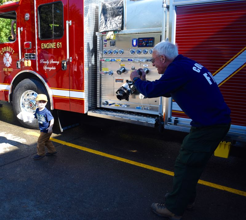 OUTLOOK PHOTO: MATT DEBOW  - Isaiah Warren, 2, pauses briefly from his cleaning duties to let Corbett Firefighter Dennis Bryson snap a photo.