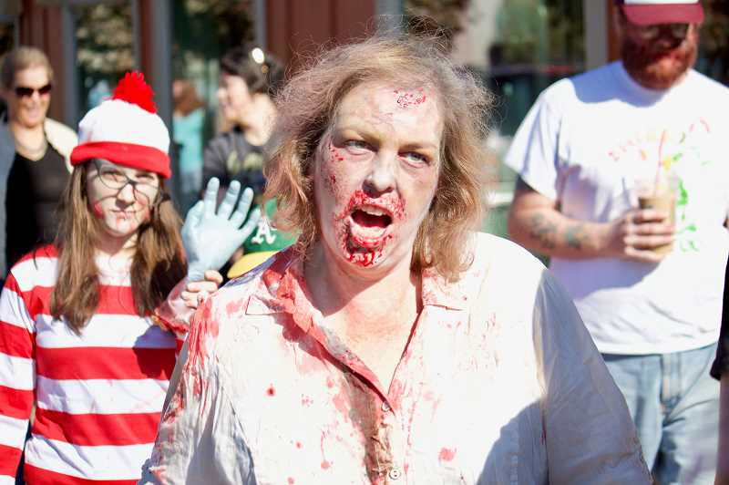 OUTLOOK PHOTO: CHRISTOPHER KEIZUR - Julie Price, one of the founders of the Gresham Zombie Walk, leads the undead horde throughout downtown Gresham on Saturday, Oct. 13.
