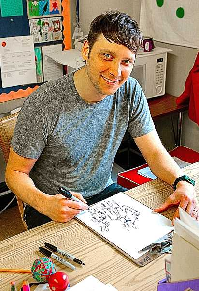 DAVID F. ASHTON - Sitting at his desk in his Woodstock Elementary School classroom, after his students have left for the weekend, award-winning cartoonist Aron Nels Steinke sketches his alter ego, Mr. Wolf, for THE BEE.