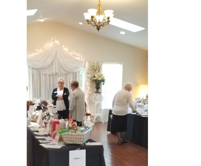 SUBMITTED PHOTO - Oregon City Woman's Club President Bev Spilseth, center in black sweater, chats with an auction attendee from last year's fundraising event.