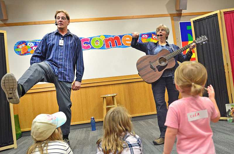 SPOKESMAN PHOTO: VERN UYETAKE - Wilsonville librarians Steven Engelfrried and Terri Wortman entertain the crowd during Family Storytime Oct. 11.