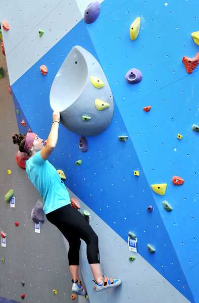 GARY ALLEN - Liz Simmons, a staff member at the Hadlock Student Center, tries her hand at a bouldering route on the climbing wall.