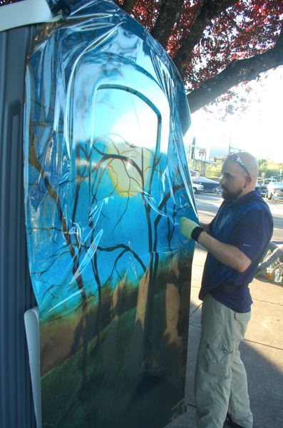PHOTO BY: RAYMOND RENDLEMAN - A reproduction of an oil painting, titled 'Totality,' from the Roger Yost Gallery, graces a portable toilet in Oregon City's Municipal Parking Lot.