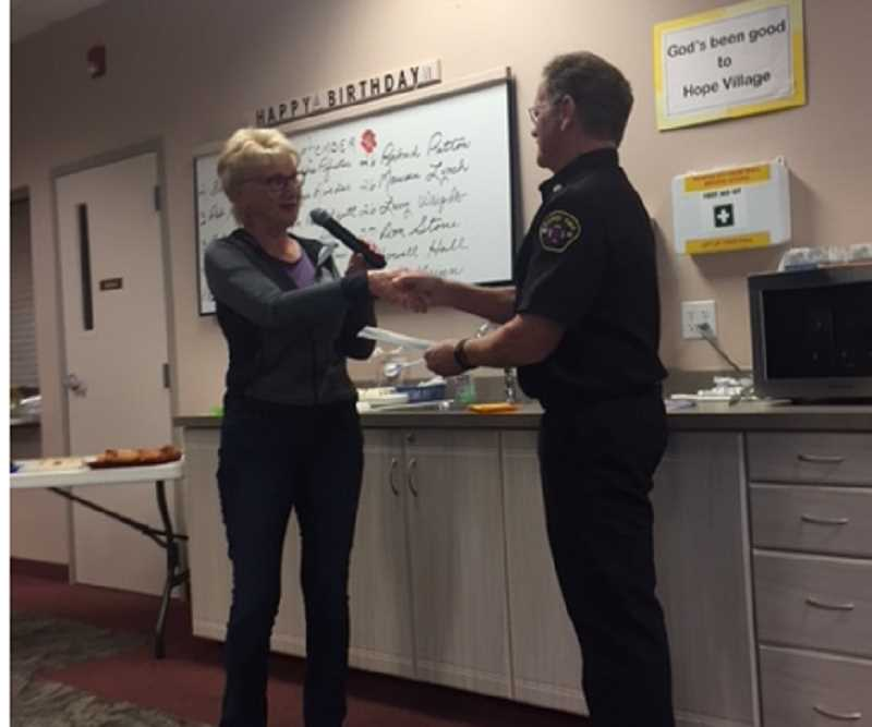 Canby Fire Chief Jim Davis accepts a $200 donation on behalf of the Dr. Richard Davies First Responsder Fund from the Hope Village community.