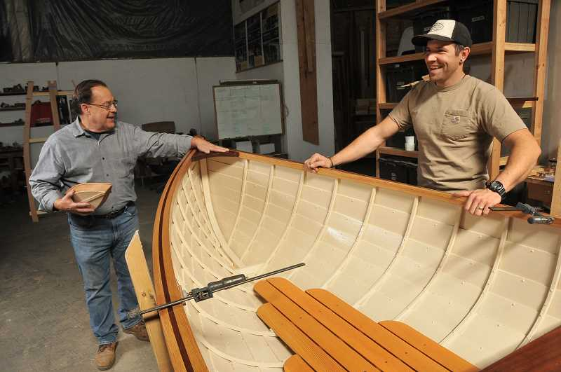 Peter Crim, left, and Nathan Nelson discuss a boat being built by students at Wind & Oar Boat School.