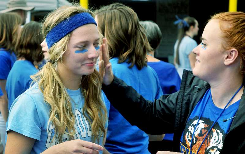 SETH GORDON - Newberg High School students paint their faces at a tailgate event earlier this fall. Student School Board representative Owen TenBrook reported that student morale has improved this fall amid a plethora of efforts have been made to better engage students and support staff.