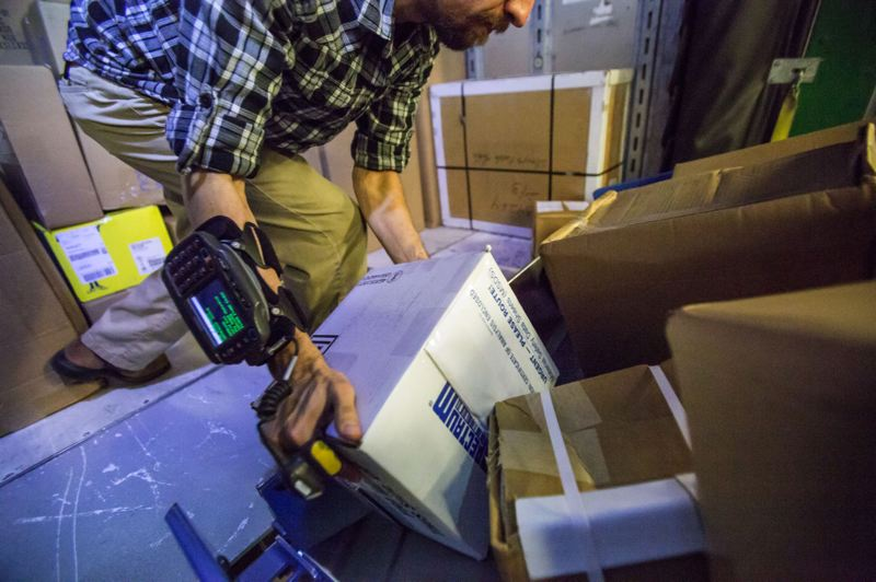 PAMPLIN MEDIA GROUP: FILE - A package handler sorts packages at the FedEx facility in Troutdale. The company is looking to fill 700 seasonal package hander positions  in its Portland-area ground division as well as 100 full-time, permanent positons in its Portland Express division.