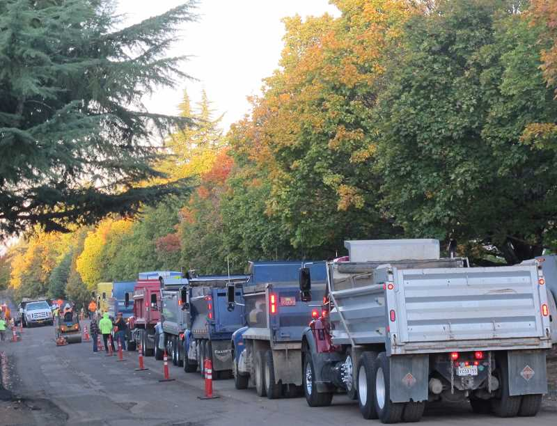 PHOTO BY BILL GALLAGHER - Trucks lined up headed westbound on SW Vermont as part of the PBOT re-paving project.