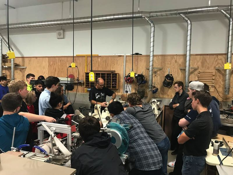 COURTESY PHOTO - Students gather round to watch a cabinetry installation tool.