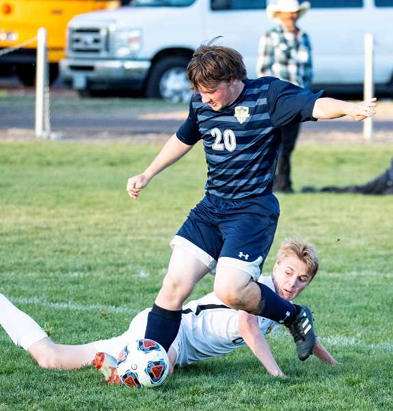 LON AUSTIN/CENTRAL OREGONIAN - Crook County defender Mitchell Bennett plays the ball away from a fallen Hood River Valley player Tuesday afternoon in Prineville. Hood River Valley dominated the competition, taking an 11-0 victory over the Cowboys.