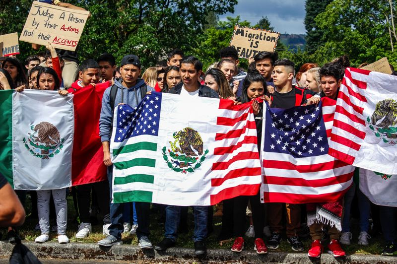 FILE PHOTO - Students hold American, Mexican and combination flags and signs during a Forest Grove High School walkout in 2016. Hundreds walked out in protest over the hanging of a sign in the school cafeteria that read 'Build a Wall.'