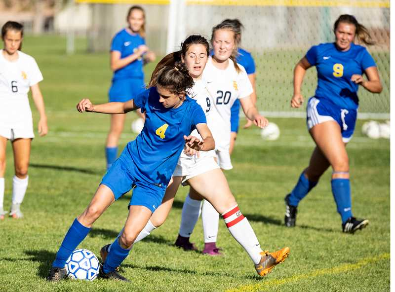 LON AUSTIN/CENTRAL OREGONIAN - Tienna Quinn plays the ball away from a Hood River Valley player during the two teams' meeting in Prineville earlier this year. Hood River Valley won Tuesday's game 6-1.