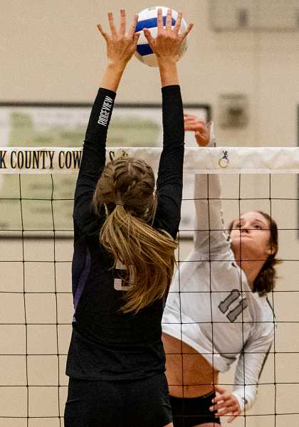LON AUSTIN/CENTRAL OREGONIAN - Liz Barker goes up for a spike. Barker finished with six kills and five blocks as the Cowgirls slugged it out with the Ridgeview Ravens Tuesday night.