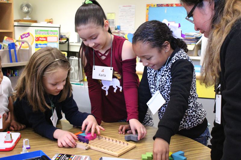 STAFF PHOTO: OLIVIA SINGER - Volunteers work with small groups during the before-school STEM Club at Cornelius Elementary School.