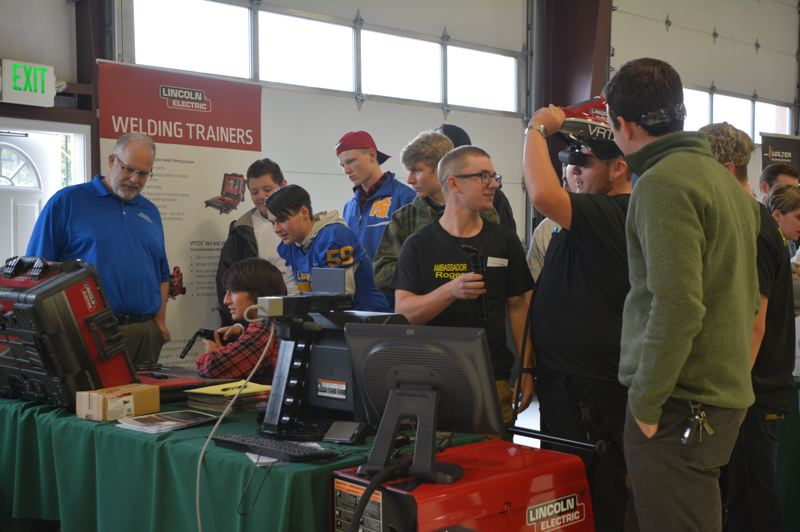 SPOTLIGHT PHOTO: COURTNEY VAUGHN - High school students test out welding simulation tools during a makers fair held Oct. 5 at the Oregon Manufacturing Innovation Center in Scappoose. Portland Community College will soon build a site in Scappoose near OMIC, offering advanced manufacturing training.