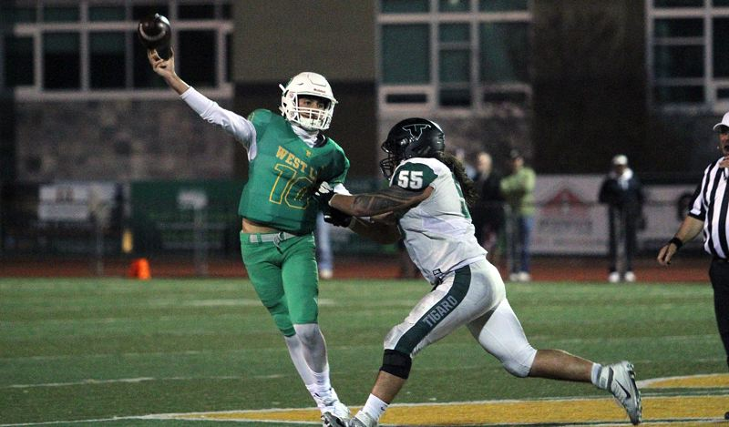 TIDINGS PHOTO: MILES VANCE - West Linn junior quarterback Ethan Coleman throws under pressure from Tigard senior Isala Porter during the Lions' 23-21 loss at West Linn High School on Friday night.