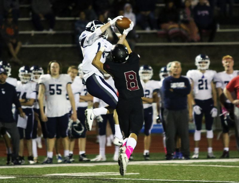TIMES PHOTO: DAN BROOD - Lake Oswego junior Thomas Dukart goes up high as he battles Tualatin's Cade McCarty for the ball during Friday's game. Dukart made the catch and got to the end zone to complete a 99-yard touchdown pass play.