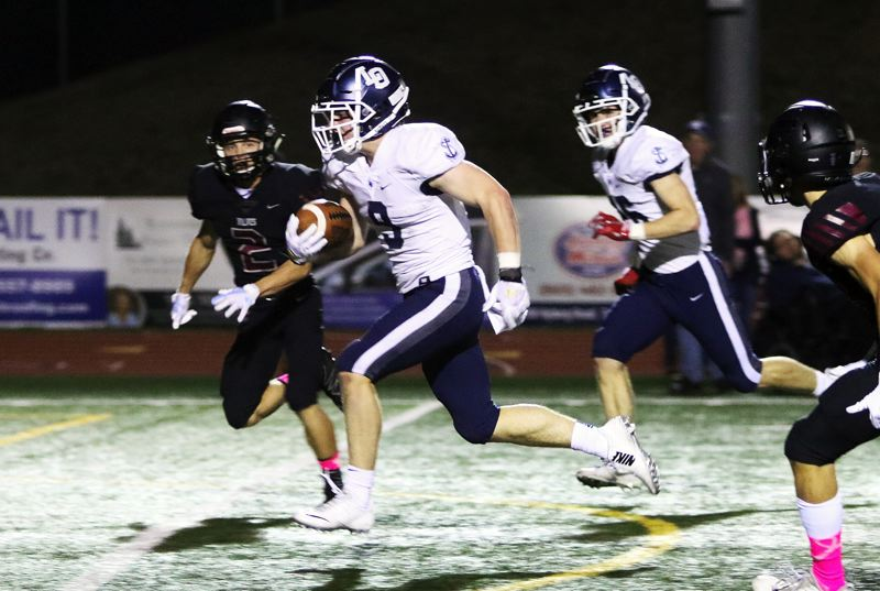TIMES PHOTO: DAN BROOD - Lake Oswego junior Casey Filkins (9) is on his way to the end zone to complete a 32-yard touchdown run in the first quarter of Friday's game at Tualatin.