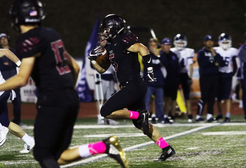 TIMES PHOTO: DAN BROOD - Tualatin senior running back Kyle Kamp runs for 37 yards on this play to set up a second-quarter Timberwolf touchdown.