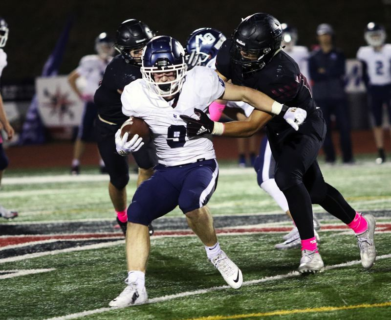 TIMES PHOTO: DAN BROOD - Lake Oswego junior Casey Fillkins tries to get away from a Tualatin defender during Friday's game.