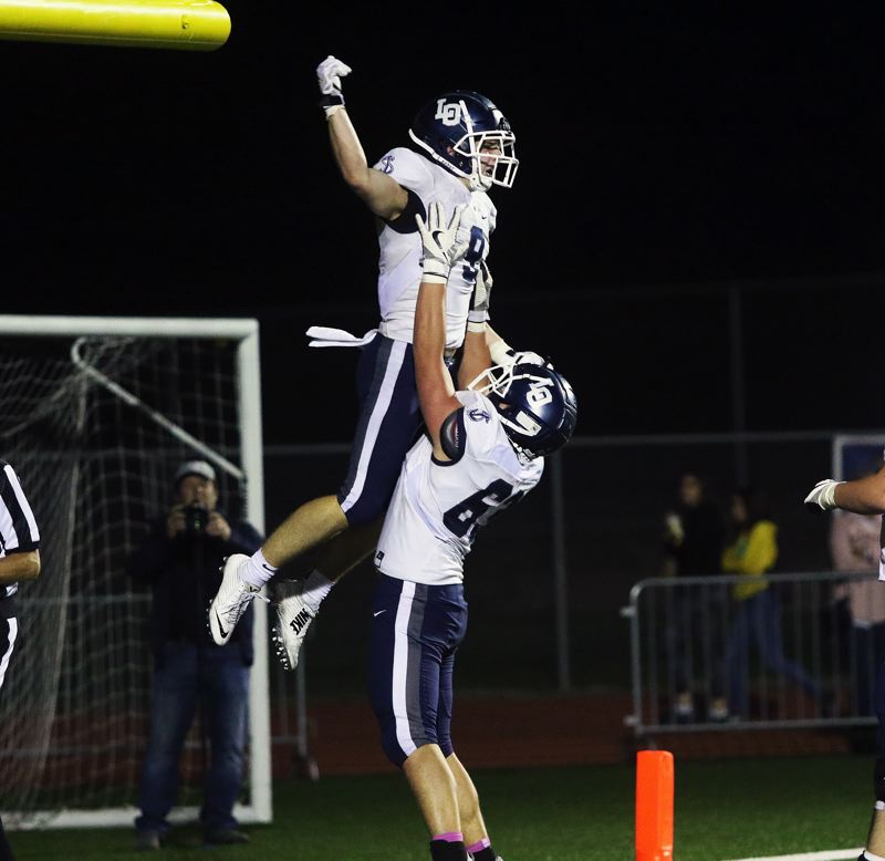 TIMES PHOTO: DAN BROOD - Lake Oswego junior Casey Filkins (left) celebrates with senior lineman Tanner Hall following a Laker touchdown in the 28-21 win at Tualatin.