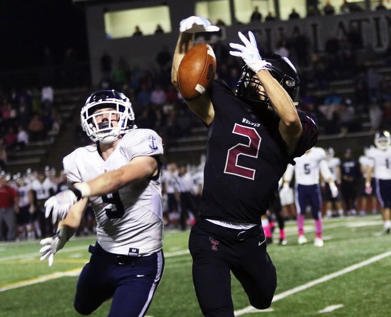 TIMES PHOTO: DAN BROOD - Tualatin senior Caden Dickson (right) and Lake Oswego junior Casey Filkins battle for a thrown ball during Friday's game.