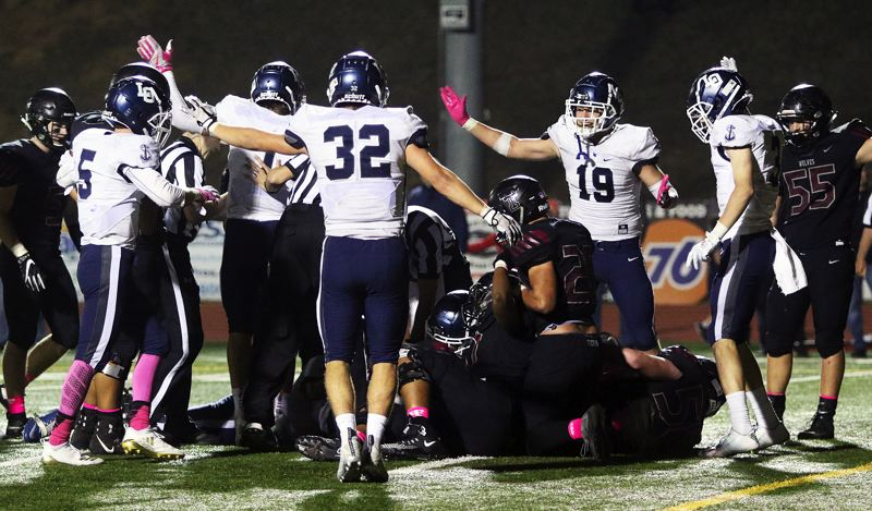 TIMES PHOTO: DAN BROOD - Members of the Lake Oswego football team, including Gabe DeVille (32) and Marshall McGuire (19) point the Lakers' direction after recovering a Tualatin fumble during Friday's game.