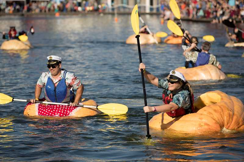 TIMES PHOTO: JAIME VALDEZ - Paddlers participate in one of four categories in the West Coast Giant Pumpkin Regatta held Saturday at the Lake at Tualatin Commons.