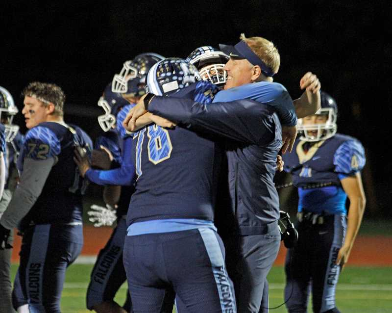STAFF PHOTO: WADE EVANSON - Liberty head coach Eric Mahlum hugs a couple of his players after the Falcons' game against Sherwood, Oct. 19, at Liberty High School.