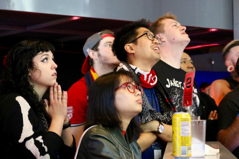 TRIBUNE PHOTO: ZANE SPARLING - Spectators watch with rapt attention during BumbleBash 3 on Sunday, Oct. 21 at Ground Kontrol arcade in Portland.