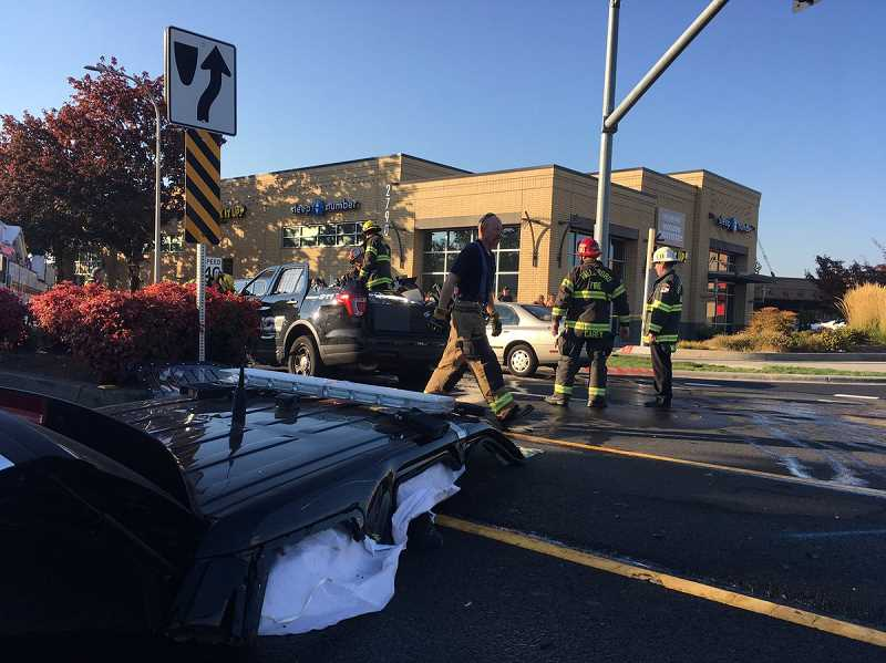 COURTESY HILLSBORO FIRE DEPARTMENT - Firefighters remove the hood of a Hillsboro patrol vehicle to extricate a cadet trapped inside after a crash on 185th Avenue and Evergreen Road on Sunday, Oct. 21, 2018.