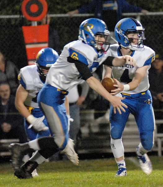 MATT RAWLINGS/ESTACADA NEWS - Brody Connell hands the ball to Jason Slawter during the Cowboys' 28-20 loss at Estacada. Slawter scored a touchdown for the Cowboys, while Connell carried the ball 10 times for 63 yards and completed eight of 16 passes for 118 yards and a touchdown in the game.