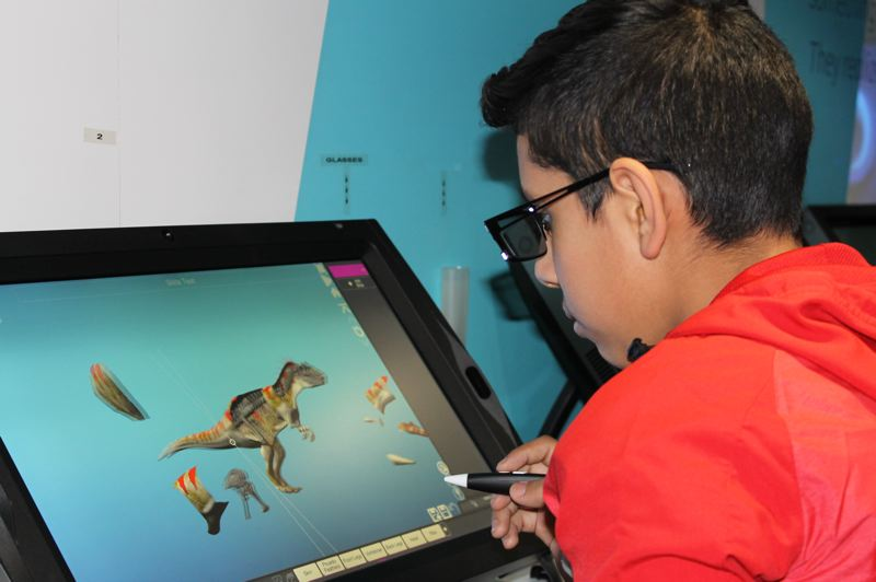 OUTLOOK PHOTO: TERESA CARSON - A Clear Creek seventh grader, wearing 3D glasses, dissects a dinosaur during a mobile classroom visit courtesy of zSpace, a high-tech firm.