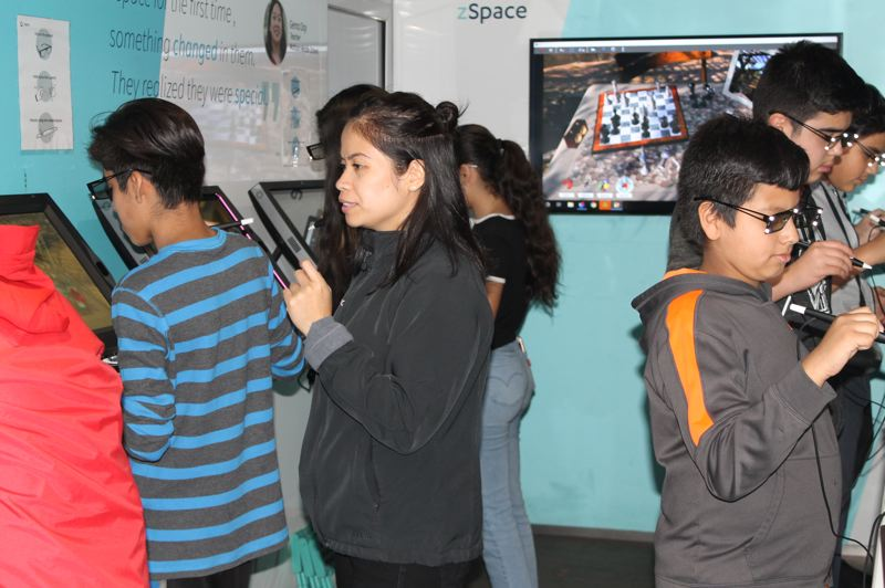 OUTLOOK PHOTO: TERESA CARSON - A zSpace educator (center, in grey fleece) guides the Clear Creek students as they use virtual reality to study science.