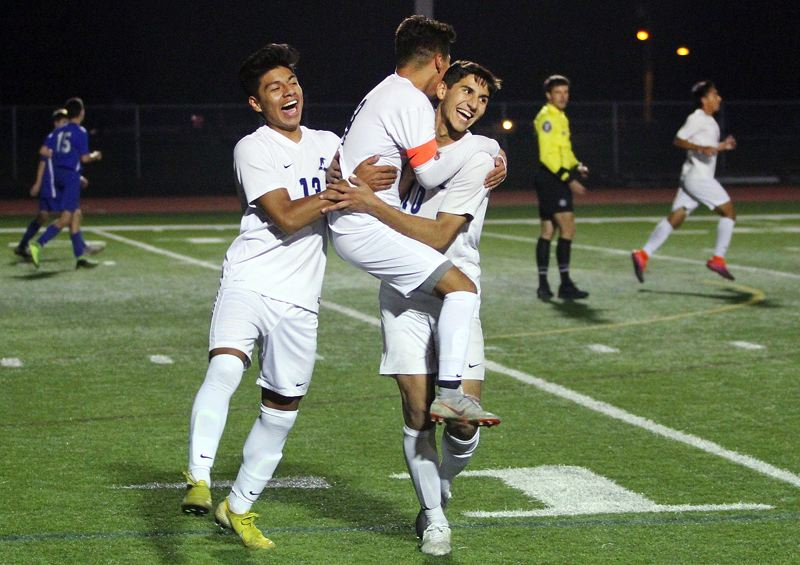 PAMPLIN MEDIA GROUP PHOTO: MILES VANCE - Liberty's Rudy Salinas Solorio (center) celebrates with teammates after scoring the first goal in his team's 2-0 win at Newberg on Monday.
