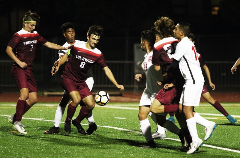 TIMES PHOTO: DAN BROOD - Sherwood High School senior Caden Brandt (8) looks to kick the ball during a scramble in front of the McMinnville goal.