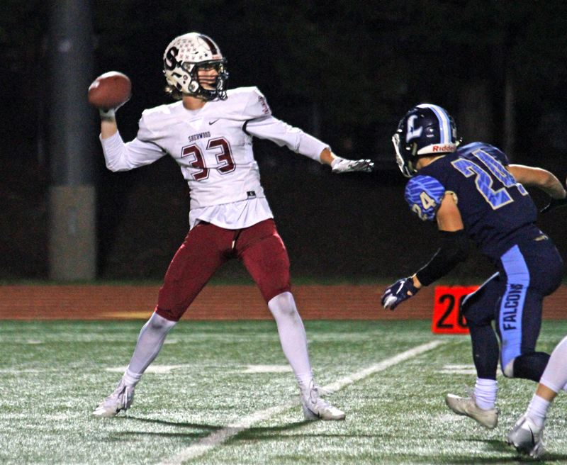 PMG PHOTO: WADE EVANSON - Sherwood senior receiver Charlie Bullfinch (left) gets ready to throw a pass off a reverse during Fridays game at Liberty.
