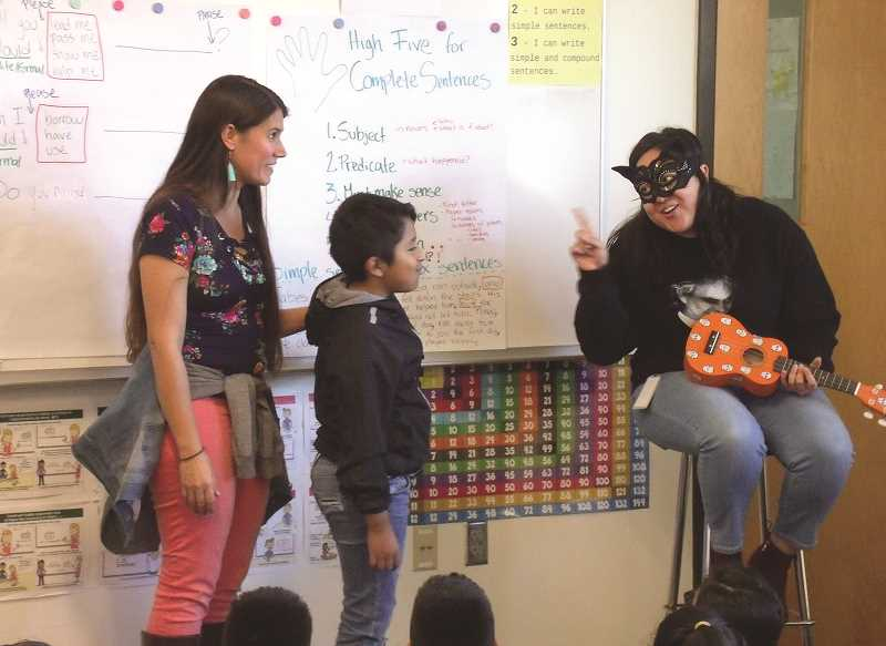 JUSTIN MUCH - Teachers and authors Kelly Carlos Freeman, left, and Fabiola Gavina Zavala, right, are helped out by Washington Elementary School fourth-grader Juan Alcantara Santos as they tell their story about Senora Bones and her Guitarrita.