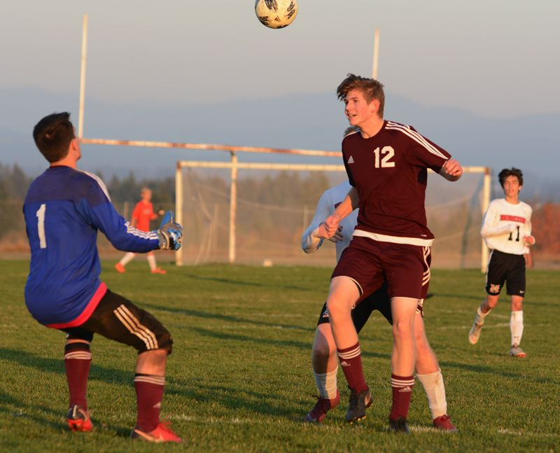 OUTLOOK PHOTO: DAVID BALL - Damascus Christians P.J. Janzen plays a header back to Eagles goalie Luke Nelson during the second half.