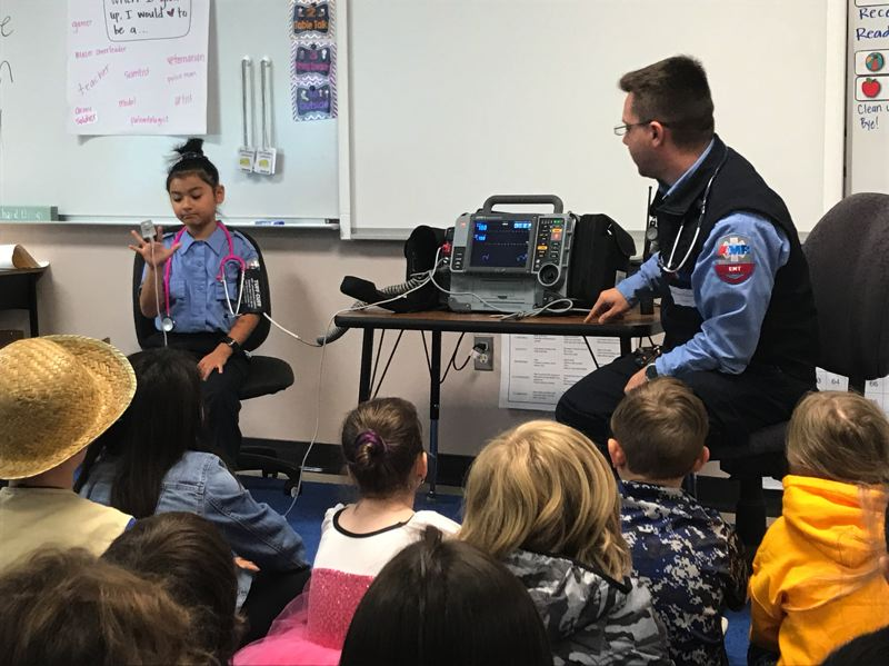 Third-grader Abbigail Hansen monitors her pulse using equipment provided by her father, AMR paramedic Michael Hansen, who presented to a group of first- and second-grade students.