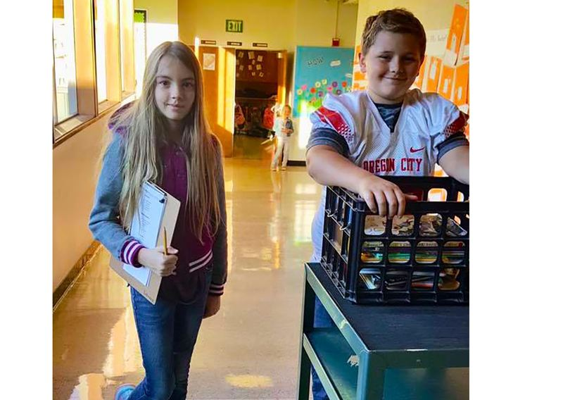 Fifth-graders Lea Thompson Niemeier and Trent Wade collect library books from classrooms each morning so they can be checked in before the students visit the library.