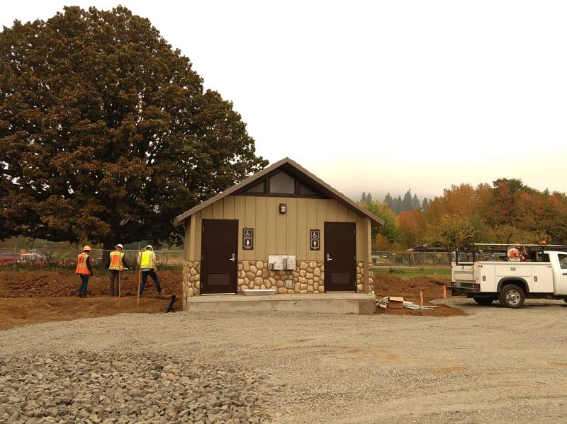 SPOTLIGHT PHOTO: COURTNEY VAUGHN - A construction crew from Tapani Inc. surveys the area immediately surrounding a recently installed restroom at Chief Concomly Park in Scappoose.