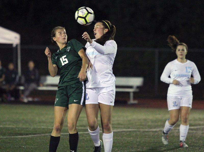 REVIEW PHOTO: MILES VANCE - Lakeridge sophomore midfielder Sarah Wittig (center) heads the ball past Tigard's Lydia Emory during her team's 2-1 win at Tigard High School on Tuesday.