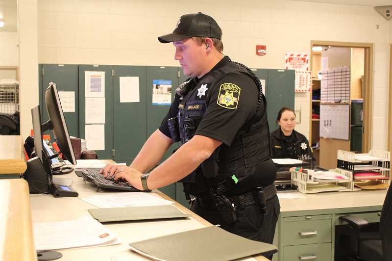 HOLLY GILL/MADRAS PIONEER - Corrections deputies Buddy Wallace and Cassandra Ruwaldt check inmates in through the Jefferson County Correctional Facility's booking area.