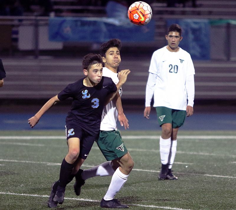 PAMPLIN MEDIA GROUP PHOTO: DAN BROOD - Lakeridge freshman forward Ryan Sze battles for the ball during his team's 1-1 tie against Tigard at Lakeridge High School on Tuesday.