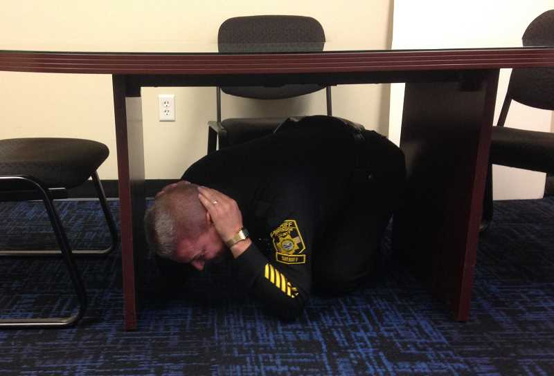 SUBMITTED PHOTO - Jefferson County Sheriff Jim Adkins demonstrates how to take cover in the event of an earthquake on  Oct. 18, during the annual Great Oregon ShakeOut drill. The message officials and emergency managers want people to remember is to 'Drop, Cover and Hold On.'