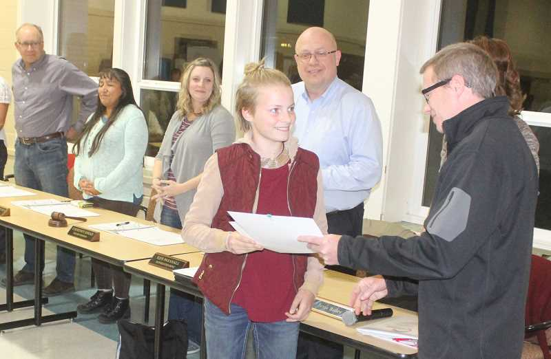 SUSAN MATHENY/MADRAS PIONEER - Kerick Adams, the teacher at Big Muddy School, presented an award to student Sierra Adams for excelling in both English literature and math on the state tests.